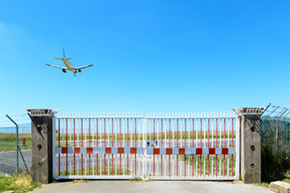 Airplane flying over a closed gate